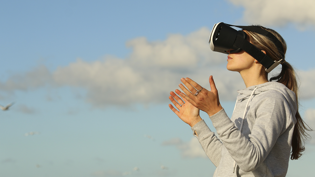 Woman with VR Glasses in front of sky